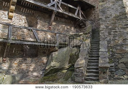 The photo shows an old, ancient stone staircase. They are made of coarse-grained, irregularly shaped stone. They are an architectural element of the Czocha castle located in the village of Leśna, in south-western Poland. They rise along the building wall,