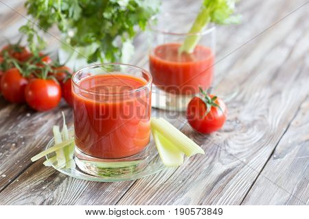 Tomato juice in a glass with celery and tomatoes on a wooden table