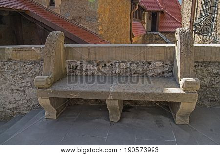 The photo shows an old stone bench. It stands beside a stone wall. At the back you will see the walls and roofs of the castle buildings. It is an architectural element of the castle of Czocha in the village of Lesna, in south-western Poland.