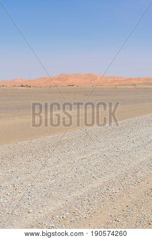 Empty rocky desert road to Erg Chebbi in the Moroccan Sahara, Africa.