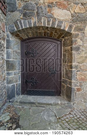 The photo shows an old wooden door. The door is painted brown paint. They are embedded in a brick wall made of regular stones. They have decorative, iron fittings painted black. These are exterior doors. They are an architectural element of the chateau of