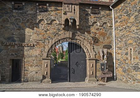 The photograph shows the big, double leading gate to the courtyard of the historic castle \ finding