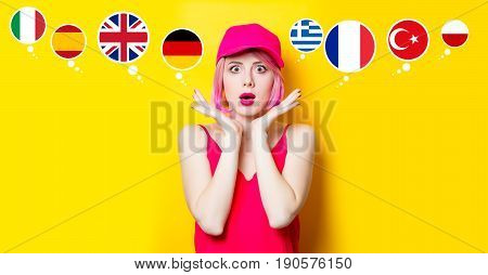 portrait of beautiful surprised young woman in cap with country flags on the wonderful yellow studio background