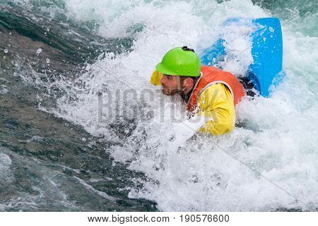 Man in a kayak about to be submerged and go underwater at an eddy with fast flowing water