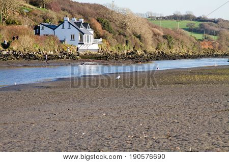 View up the estuary at Newport, Ceredigion, West Wales, United Kingdom.  The tide is out and there is one house on the river bank.