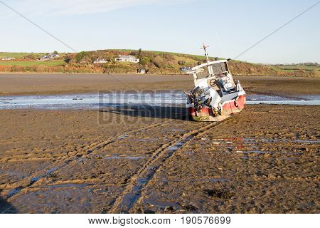 Grounded Boat At Low Tide On A Sandy Beach