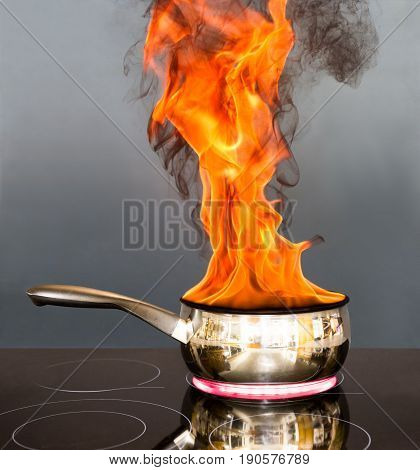 Saucepan on a hob with flames coming out of it like a chip pan fire