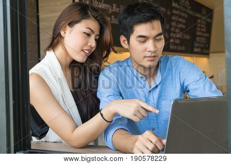 Close up Asian yong couples surfing on interne with laptop in coffee shop.