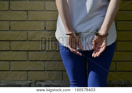 Fragment Of A Young Criminal Girl's Body With Hands In Handcuffs Against A Yellow Brick Wall Backgro
