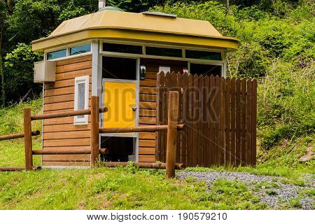 Closeup of wooden public toilets in a woodland park area in South Korea.