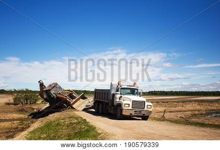 A backhoe attached to gravel truck sliding dangerously into a ditch in an afternoon sunny summer countryside landscape