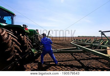 A middle aged man in blue coveralls repairing a hitch on a plow attached to a tractor with big wrench in a cultivated field in a rural landscape