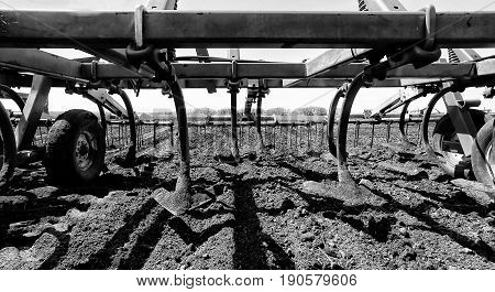 Close up of shovels on an agricultural cultivator sitting on a brown dirt field in black and white