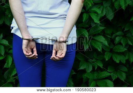 Fragment Of A Young Criminal Girl's Body With Hands In Handcuffs Against A Green Blossoming Ivy Leav