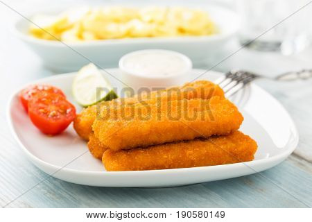 Heap of fish fingers with homemade potato salad