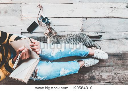 Hipster lifestyle - Girl in jeans writing diaries with retro camera smart phone and cat sit on the wooden floor. vintage film color effect and retro color style
