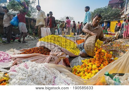KOLKATA WEST BENGAL / INDIA - FEBRUARY 13TH : Buying and selling of flowers in crowded and colorful Mallik Ghat or Jagannath ghat flower market in Kolkata on 13.02.16. One of Biggest flower markets in Asia.