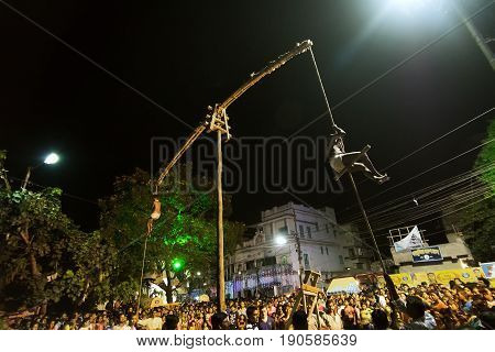 KOLKATA WEST BENGAL INDIA - 15 APRIL 2017: Two Hindu devotees are hanging in air from ropes and circling around at night. Religious sports for festival called