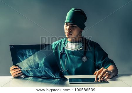 Male doctor or surgeon looking at mammogram xray film while using tablet computer in a dark room.