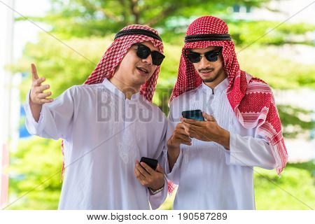 Arab man talking and using mobile phone. Two arab man business meeting discussion. Arabic international business concept. Successful Arabic businessmen.