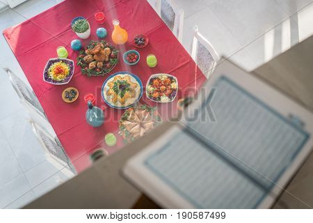 Ready served food on the table below open Koran