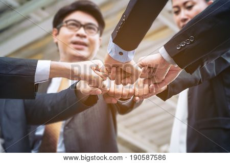 Business people or business team joining hands showing teamwork collaboration and unity. Concept of business success with teamwork in business.