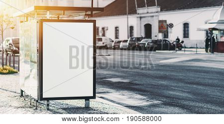 City bus stop on paving stone with empty poster blank vertical information placeholder in urban settings white clear billboard with copy space zone for text logo or your advertising messages