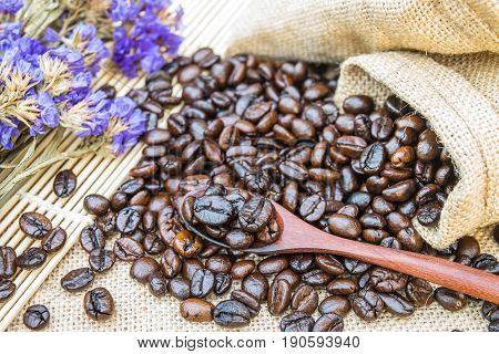 Coffee beans in sack bag with dry flower on sack background