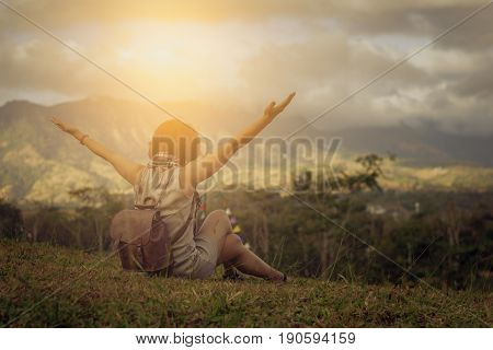 Carefree Happy Woman Enjoying Nature on grass meadow on top of mountain cliff with sunrise. Beauty Girl Outdoor. Freedom concept. Lens flare effect. Sunbeams. Enjoyment./Vintage Concept