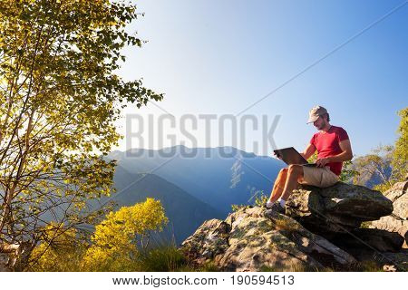Young caucasian man sitting outdoor on a rock working on a laptop pc in mountain area. Summer season, European Alps.