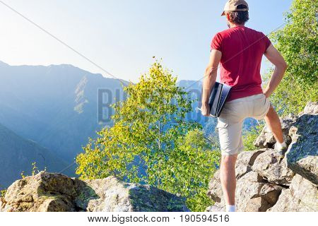 Young caucasian man standing outdoor on a rock working on a laptop pc in mountain area. Summer season, European Alps.