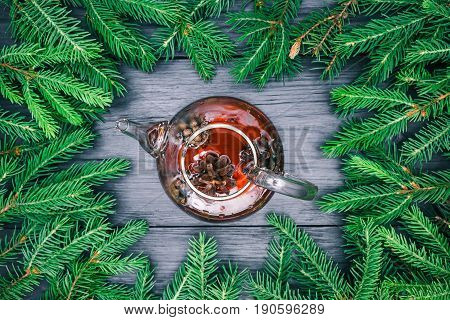 Tea in teapot wit pine cones  over black wood background with border of evergreen christmas tree twigs. Top view