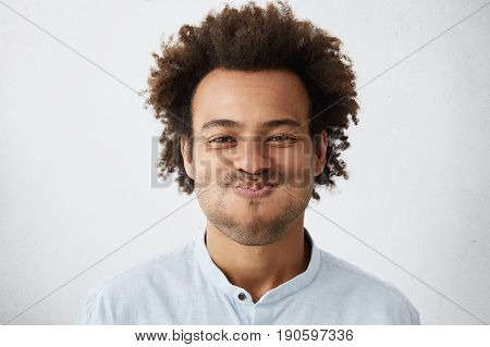 Close-up Of Childish African Student Male With Funky Hair Blowing His Cheeks Bursting Out Laughing H