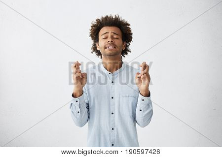 Handsome College Student Male With Head Of Curly Hair Standing Against White Background With Crossed