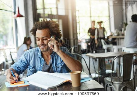 Positive Smart Black Guy With Afro Hairstyle Writing Down Information On Sticky Notes, Smiling Cheer