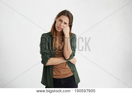 Portrait Of Beautiful European Woman With Long Hair Dressed In Green Casual Jacket Looking Exhausted