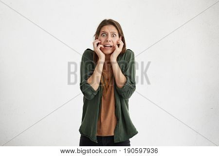 Scared Stressful Woman With Bugged Eyes Holding Hands On Her Face Looking Terrified Into Camera. Fea