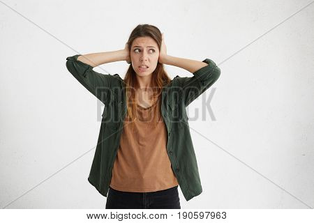 Portrait Of Attractive Young Woman In Casual Clothes Covering Her Ears With Hands Not Wanting To Hea