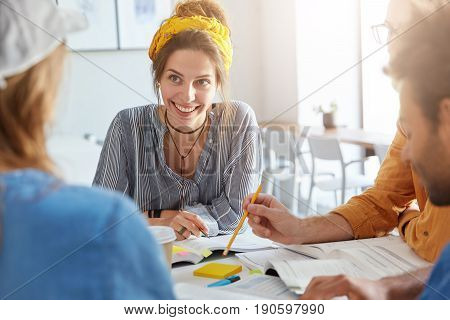 Cooperation and teamwork concept. College students sitting together having working atmosphere surrounded with books and papers discussing their future project having pleasant smiles and expressions