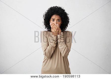 Sorrorful mixed race woman with staring look having fine crop of hair wearing brown sweater holding her hands on mouth regreting what she done looking sadly into camera. Negative emotions cooncept