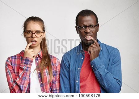 Waist Up Portrait Of Fashionable Young Interracial Couple Wearing Glasses And Shirts Having Disguste