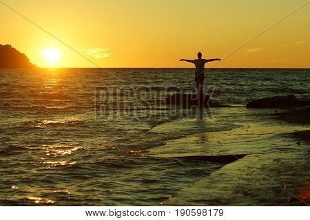Silhouette of a man standing on a rock with raised perpendicular hands on a sunset background on the seashore.