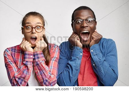 Excited Surprised Young Interracial Couple Dressed In Identical Clothes And Eyeglasses Keeping Clenc