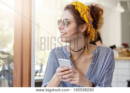 Medium Close-up Of Beautiful Woman Wearing Yellow Headband, Stripped Shirt And Sunglasses Holding Mo