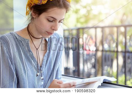 Undergraduate Student Girl With Headband Sitting With Book At Balcony Reading Something With Focused