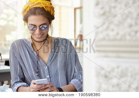 Lovely Housewife Dressed Casually Wearing Sunglasses Standing Indoors Looking With Smile In Screen O