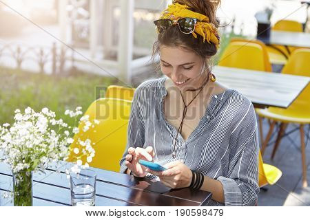 Woman Wearing Sunglasses And Scarf On Head, Casual Stripped Shirt Sitting Outside At Terrace Holding