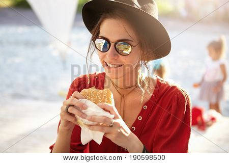 Hungry Woman In Elegant Clothes Wearing Sunglasses Holding Cheesburger Eatting It With Pleasure Isol