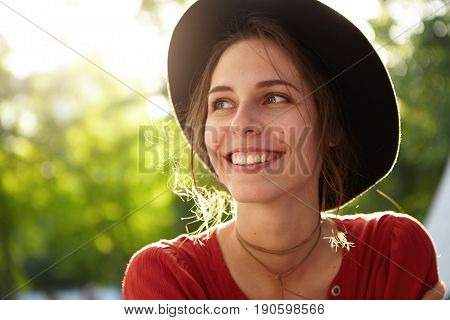 People, Nature, Resort, Summer, Vacations Concept. Sunny Portrait Of Cute Young Female In Trendy Hat