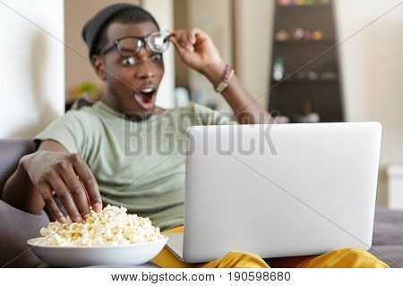 Excited Hipster Male With Dark Skin Wearing Casual T-shirt And Hat Taking Off His Glasses Looking Wi